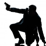 silhouette man kneeling aiming gun